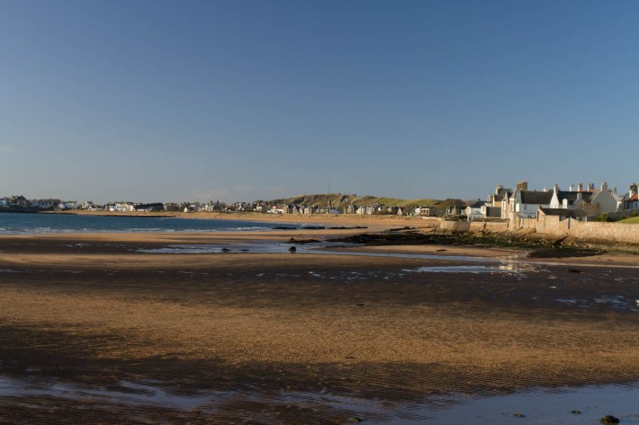 Elie, East Neuk, Fife, Scotland. Large beach. The tide is out but the sand is still damp. Houses overlooking the beach
