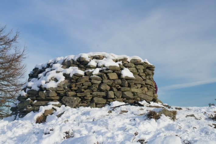 A stone cairn on top of Birnham Hill, Perthshire. Snow on the ground and blue sky