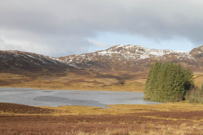 Highland Safaris, Perthshire. Snow capped mountains with a small lochan in the foreground covered in ice