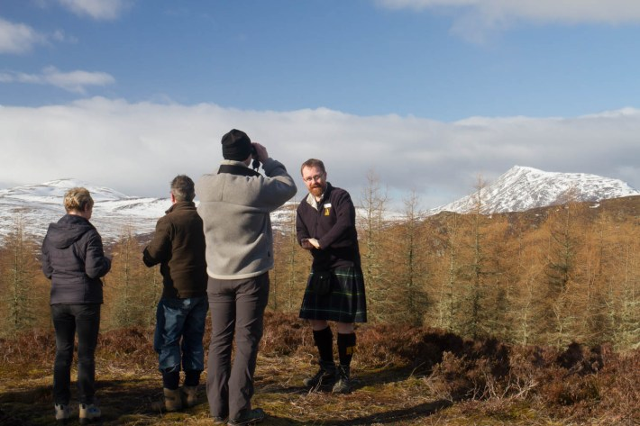 Highland Safaris, Perthshire. Tour guide in a kilt with a group of people on the hills. Man looking through binoculars