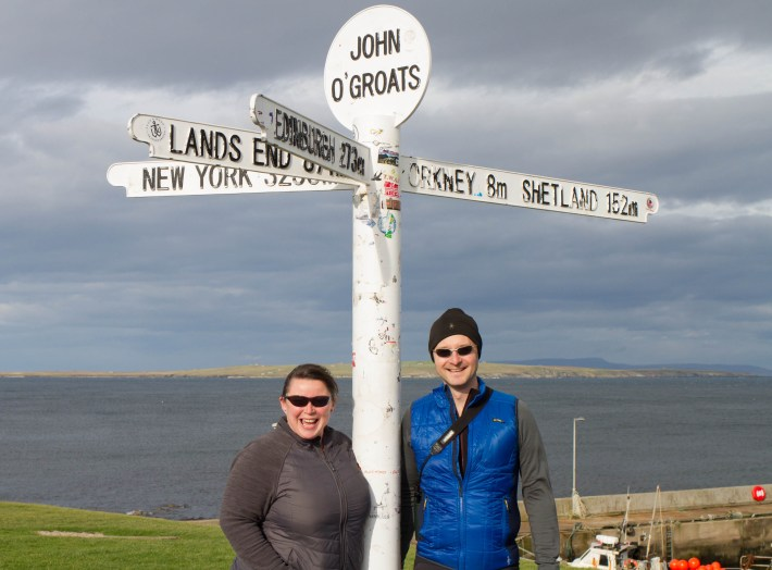 Scottish Travel Blogger. Man and woman stood beneath the John O'Groats mileage sign post.
