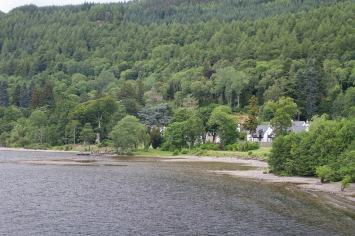 Kenmore Village, Perthshire. The shoreline of loch Tay. Trees on the hillside and houses partially visible