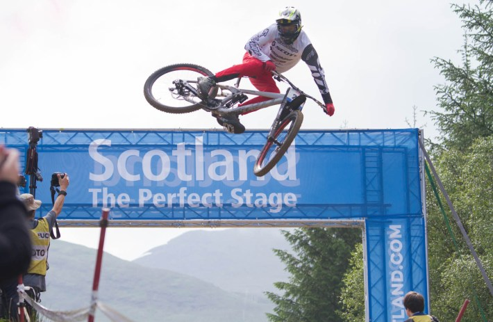 A mountain bike mid air off a jump at the Fort William World Mountain Bike Championships