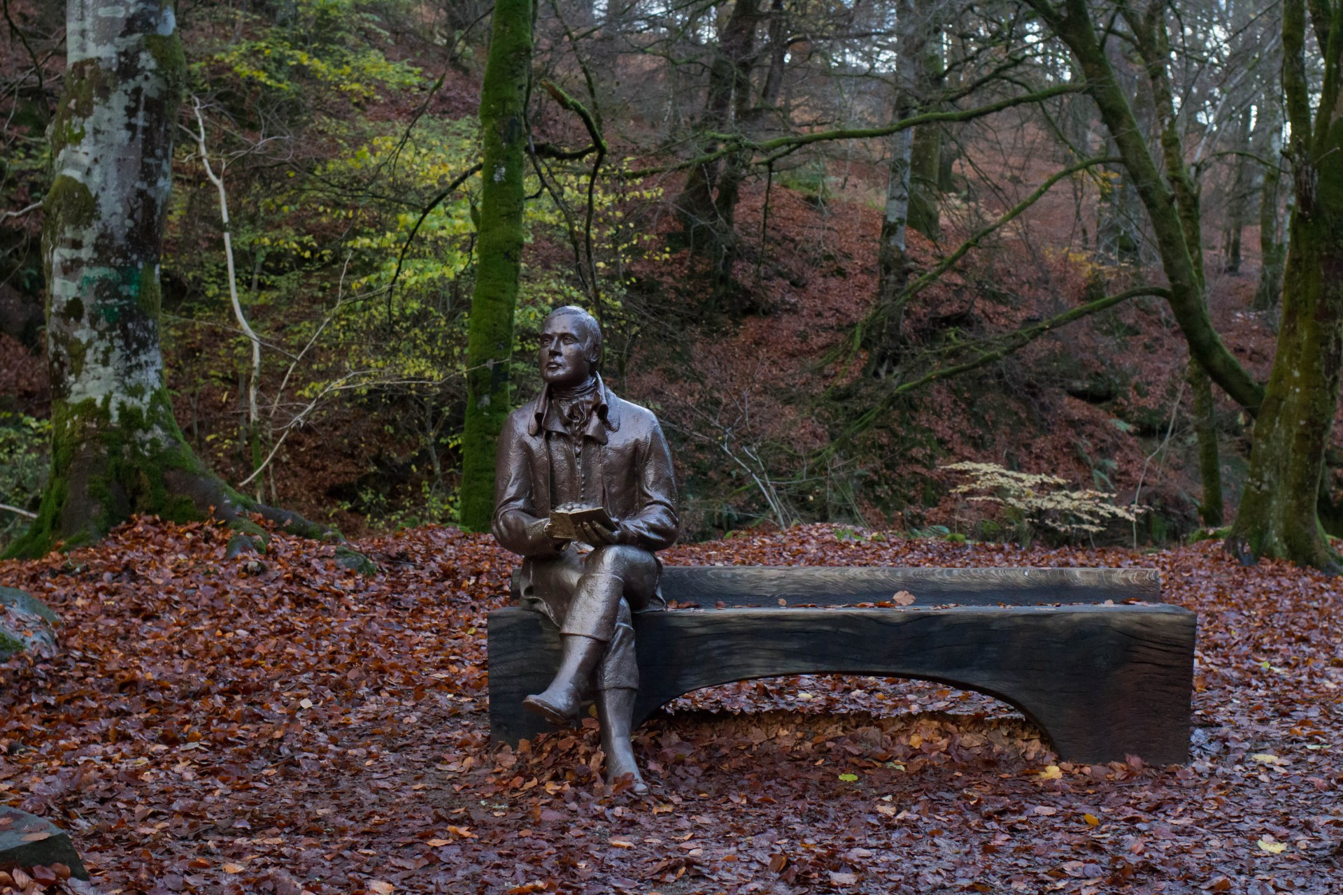 Robert Burns statue. He sits of a bench in the woods