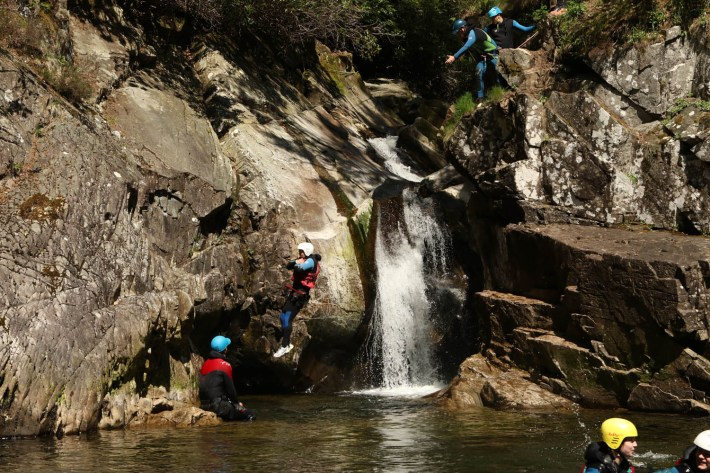 Cayoning in Perthshire. Man jumping off a rock into a large pool