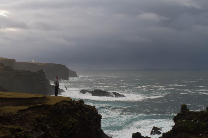 Esha Ness cliffs, Shetland. Man stood on the cliffs. Moody sky, lighthouse in the distance. The sea is crashing against the rocks