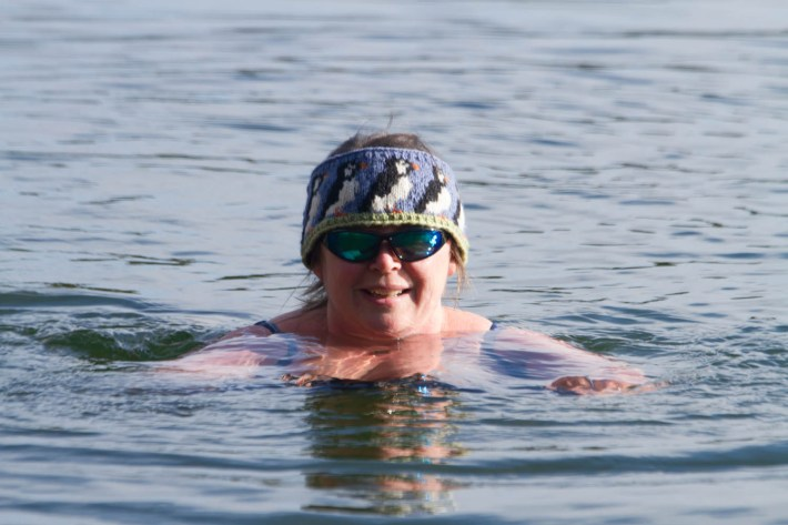 Photo of a woman in the water. The sun is shining and she is wearing sun glasses and a headband with puffins on