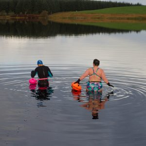 Image of two women in a loch in Scotland. One is wearing a wetsuit and the other is wearing a swimsuit