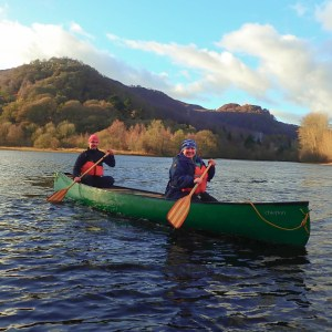Photo of a man and a women canoeing on the river in Winter in Scotland