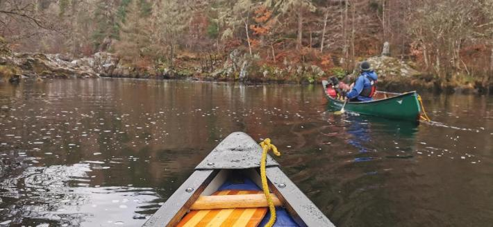 Photo of a man and his dog in a canoe on the river Tummel