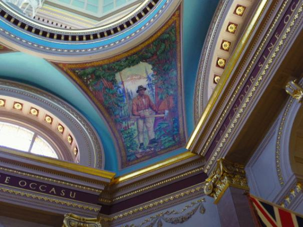 Rotunda paintings representing the four major industries: tourism, fishing, mining and lumber.