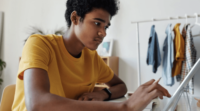 Young man using a tablet at a desk in a bedroom, looking a bit anxious