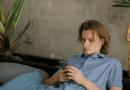 Man using phone reclining on sofa