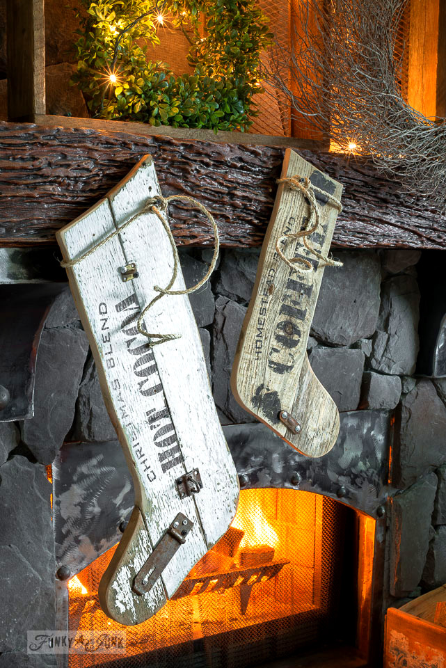 Old sign styled reclaimed wood Christmas stockings on a