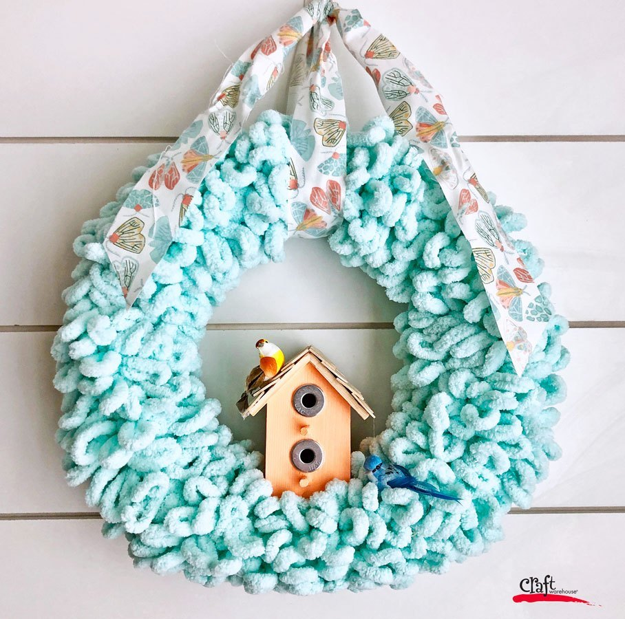 pretty blue spring wreath made from hook yarn with birdhouse