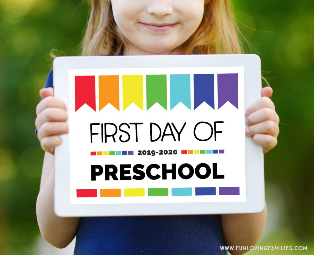 girl holding first day of preschool sign