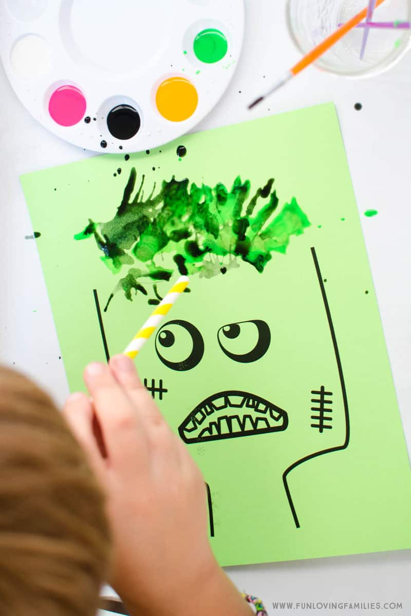 We used the zombie printable and had a blast doing blow painting with straws. Add paint all over the zombie's hair to make fun and crazy hairstyles! #kidsartproject #kidsart #kidsartactivity #zombiecraft #kidsactivity #freeprintable #funlovingfamilies