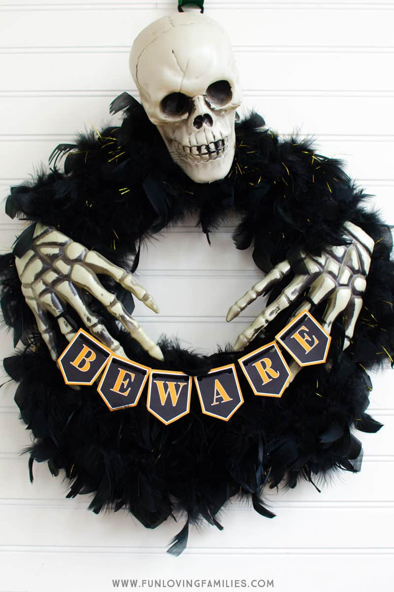 Easy DIY Halloween wreath from Dollar Store finds with free printable banner. #halloween #dollartree #dollarstoredecor #halloweendiy #halloweenwreath #halloweeprintables #funlovingfamilies