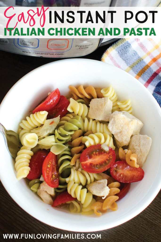 White bowl with tri-color rotini, tomatoes, and chicken