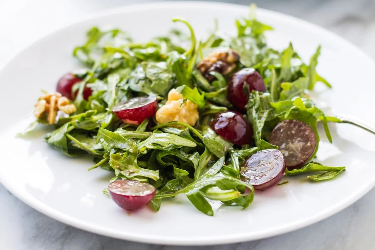 Low Fodmap Arugula Salad with Grapes is filled with peppery arugula, succulent red grapes, crunchy walnuts and a balsamic Dijon vinaigrette.