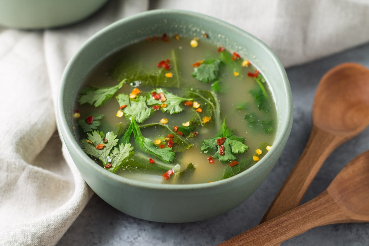 Bowl of tom yum soup with wooden spoons