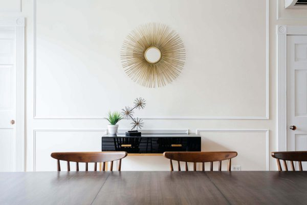 Dining room with wooden chairs, black console table and gold starburst mirror