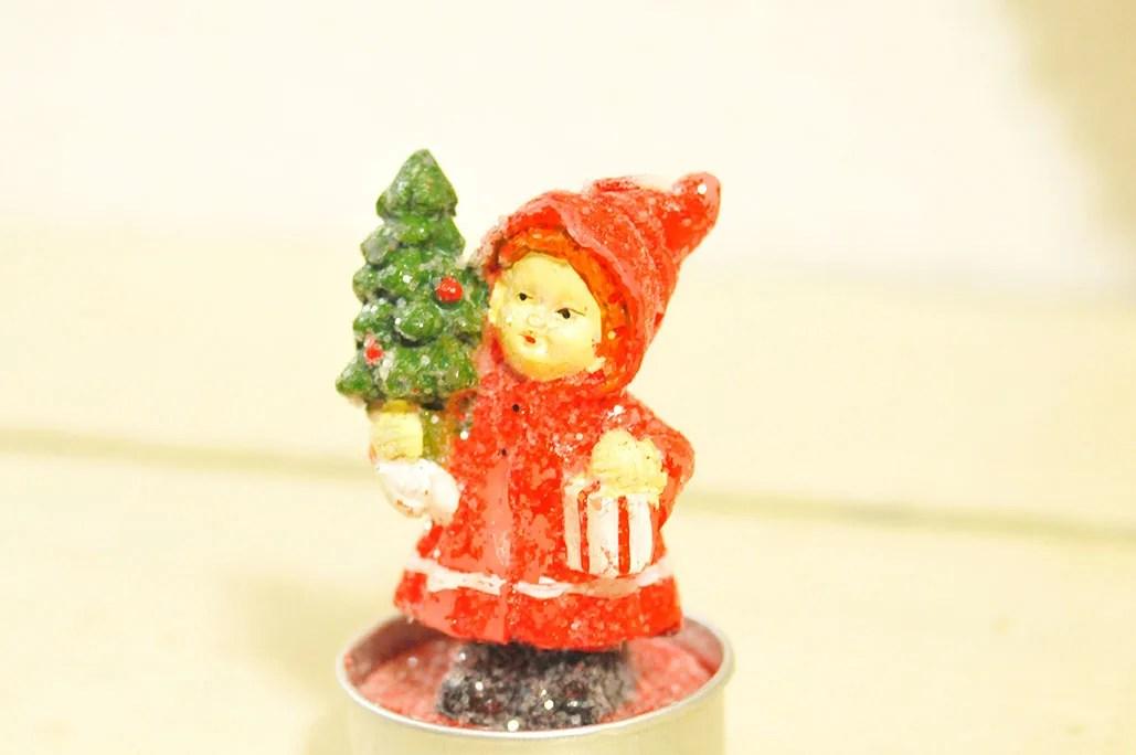 もみの木を持った赤いコートの女の子のロウソクは50円