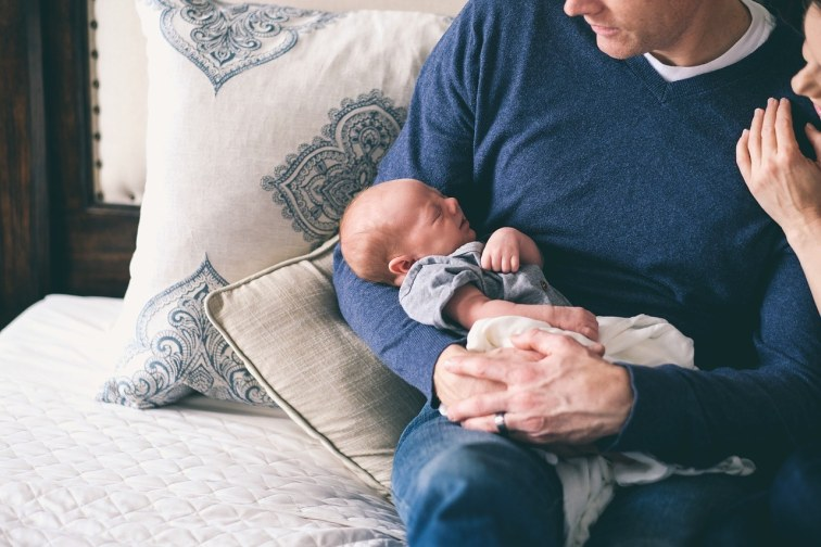 a-father-holding-his-baby-on a-baby-pillow
