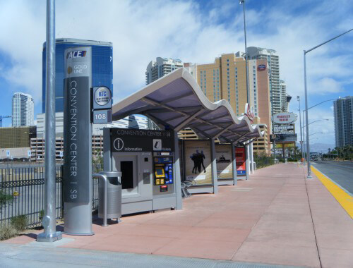 Custom designed transit bus shelter next to a road.