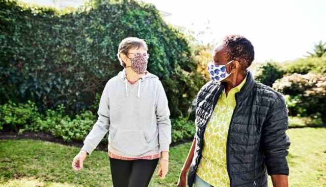 Two women walk through a park wearing face masks