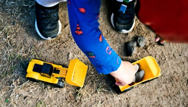 A young child plays with yellow toy trucks in the dirt