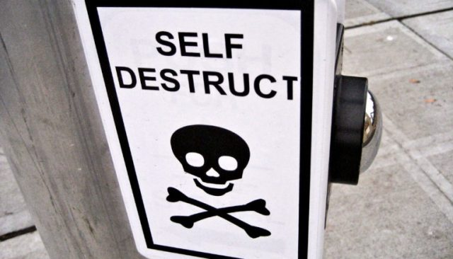 """A sign over a button at a crosswalk has a skull and cross bones on it and reads """"Self Destruct"""""""