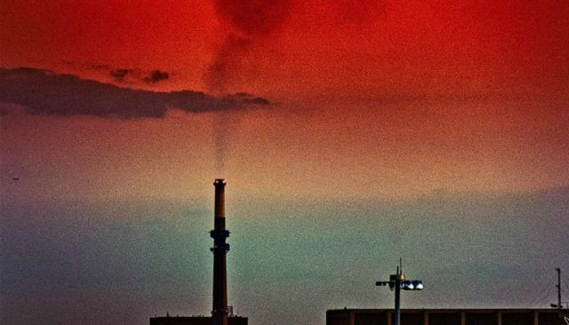 Black smoke rises from a smokestack into a blue, orange, and red sky