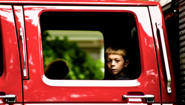child's face in extended cab window of red truck