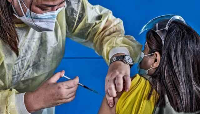 Een gezondheidswerker geeft het COVID-19-vaccin aan een zittende vrouw