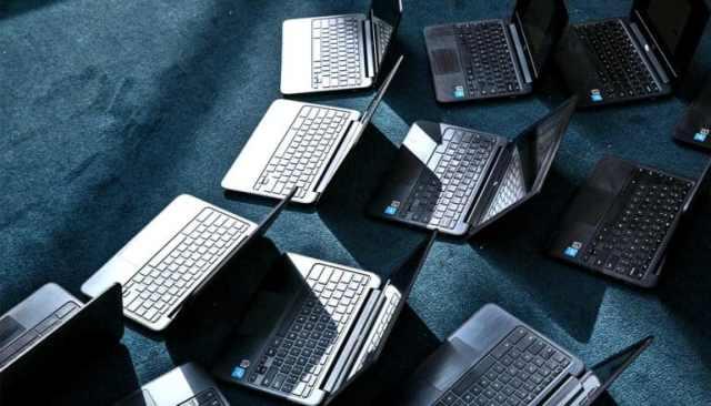 Veel laptops verspreid over een blauw tapijt