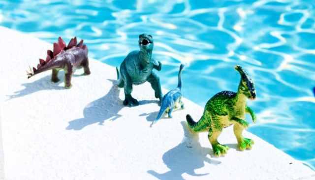 Dinosaurusspeelgoed staat aan de zijkant van een blauw zwembad