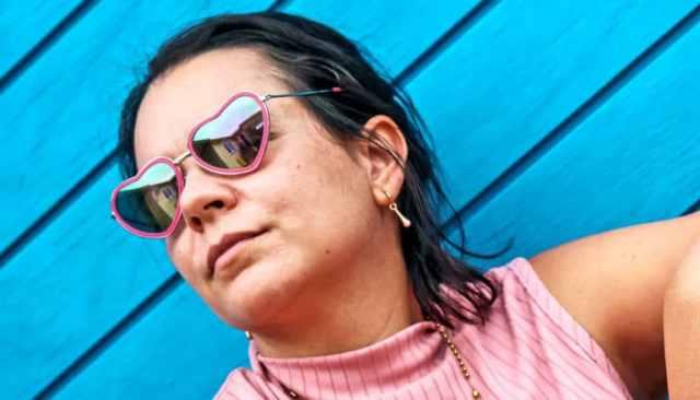 Een vrouw draagt een hartvormige zonnebril die voor een blauwe muur zit
