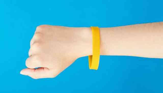 Een vrouw draagt een geel siliconen polsbandje tegen een blauwe achtergrond