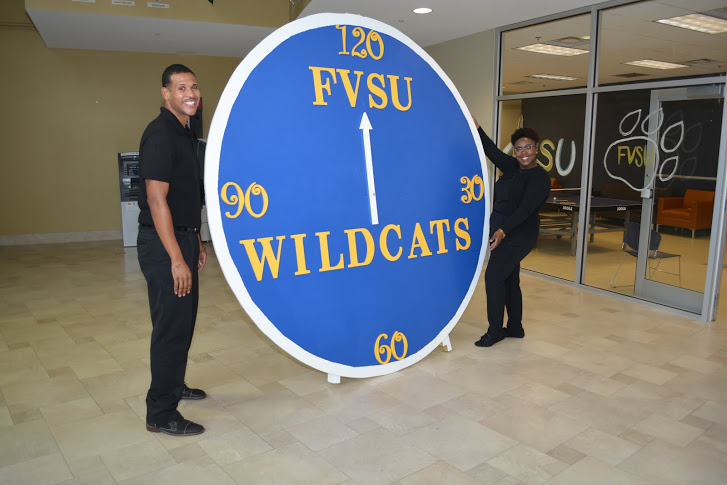 Students stand by clock display at 120th Anniversary Student Breakfast
