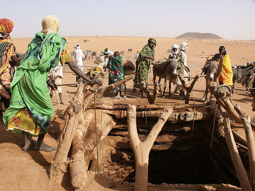 women drawing water from a well in Darfur