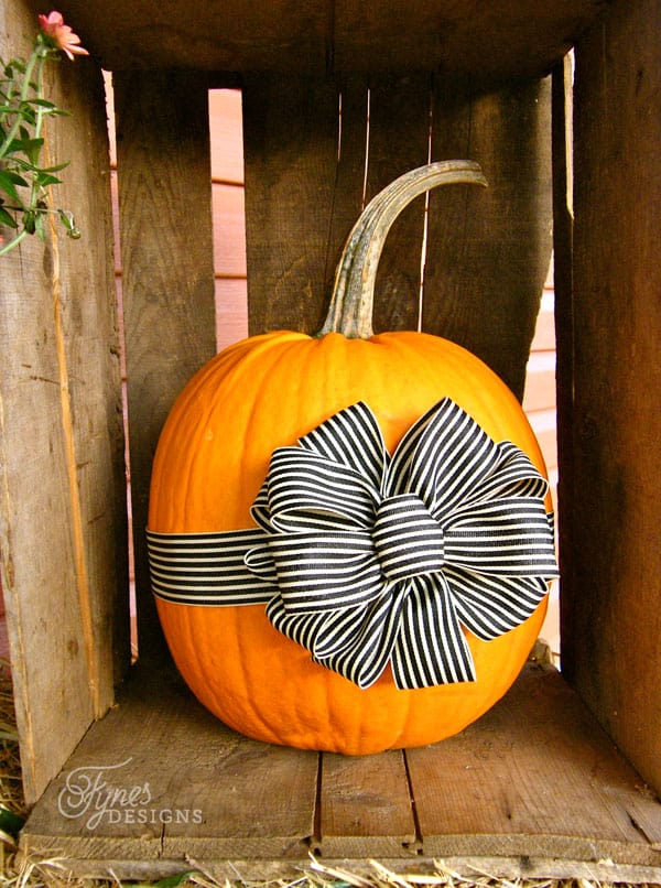 Fall porch decorating ideas- Add a Ribbon bow to your pumpkin for a unique look |  Fall Wreath by popular Canada DIY blog, Fynes Designs: image of a pumpkin in a wooden crate with a black and white stripe ribbon tied around it.