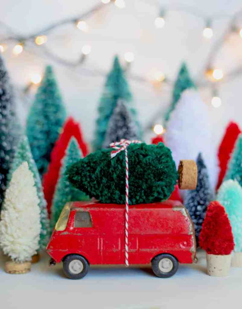 How to make your own bottle brush trees. Get everything at the dollar store |Bottle Brush Tress by popular Canada DIY blog, Fynes Designs: image of a bottle brush tree tied to a metal toy van.