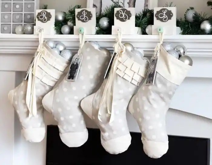 Easy to sew personalized Christmas stocking tutorial |DIY Personalized Christmas Stockings by popular Canada DIY blog, Fynes Designs: image of grey and white stockings hanging on a fireplace mantle.