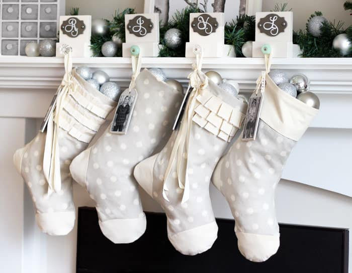 Easy to sew personalized Christmas stocking tutorial  DIY Personalized Christmas Stockings by popular Canada DIY blog, Fynes Designs: image of grey and white stockings hanging on a fireplace mantle.