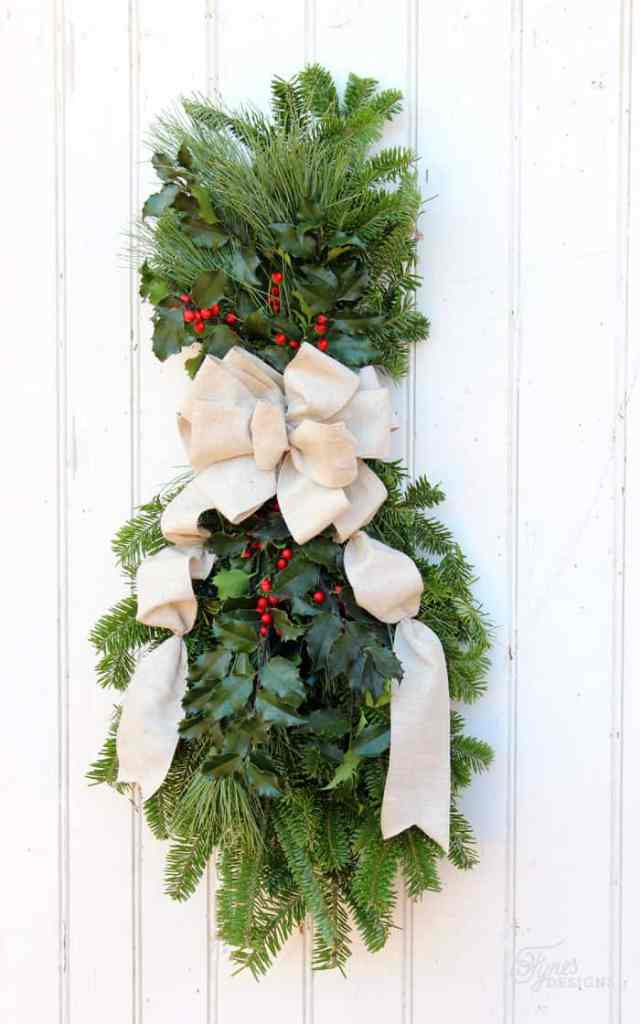 How to make a Christmas swagwreath, Easy to follow instructions featured by top US life and style blog, Fynes Designs |Swag Wreath by popular Canada DIY blog, Fynes Designs: image of a swag wreath with a cream ribbon, holly, and pine boughs.