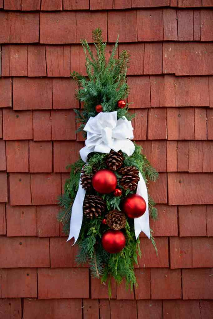 Step by step instructions how you can make a natural swag for your front door | Swag Wreath by popular Canada DIY blog, Fynes Designs: image of a swag wreath with a white ribbon pine cones and red ornaments.