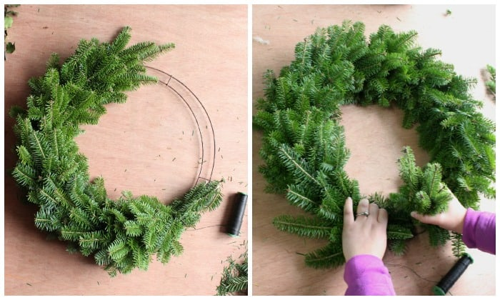 Step 4 how to make a wreath | Christmas Wreath by popular Canada DIY blog, Fynes Designs: image of a pine tree branch being attached to a flat ring with floral wire.