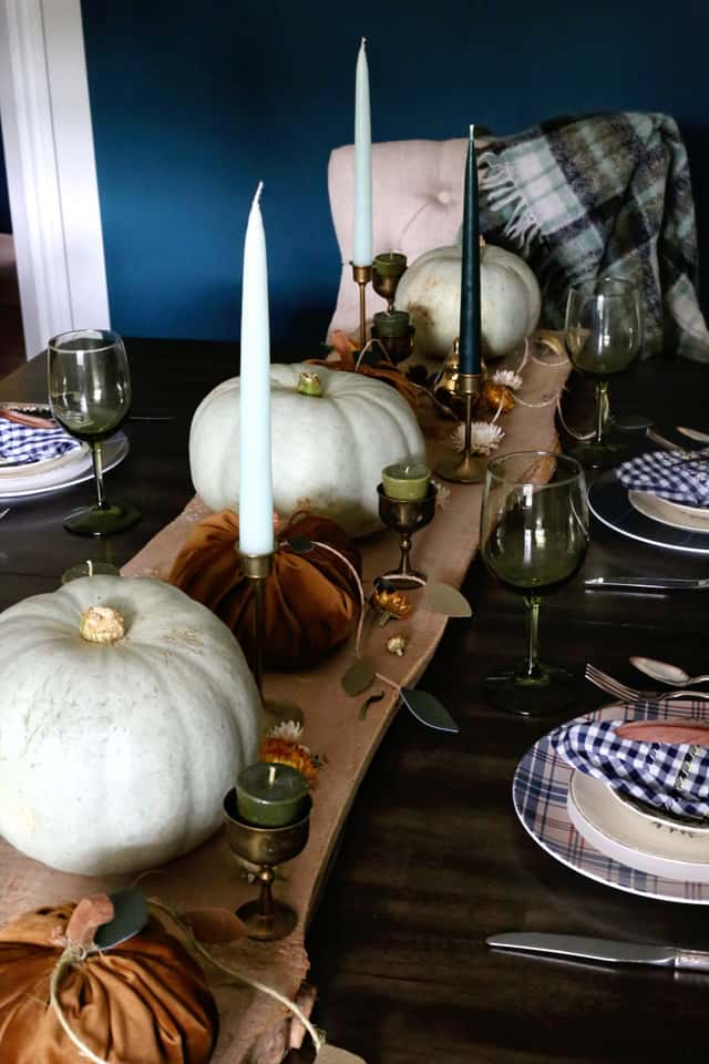 Fall centrepiece with wood an copper elements |Fabric Pumpkins by popular Canada craft blog, Fynes Designs: image of a table set with white pumpkins, fabric pumpkins, taper candles in brass candle holders, green wine glasses, and blue and white buffalo check napkins on cream color ceramic plates resting on top of blue, white, and pink plaid chargers.