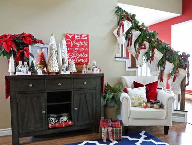 Handmade Christmas stockings hung on the banister with natural garland